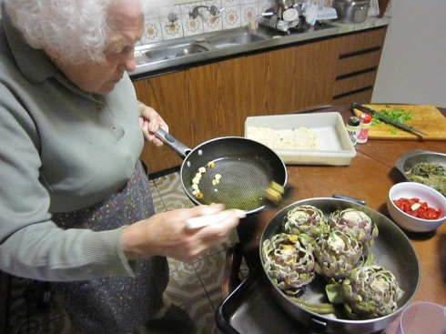 Nonna pours garlic over artichokes